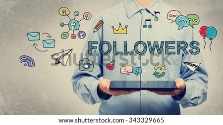 Followers concept with young man holding a tablet computer  - stock photo