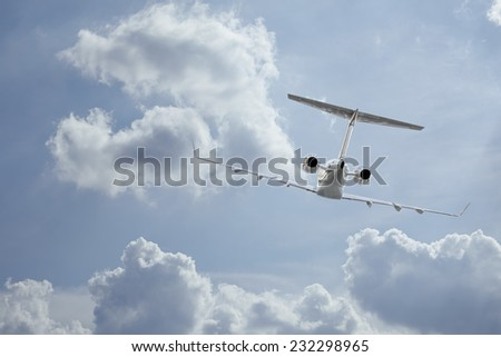 Following a private jet flying through the clouds - stock photo
