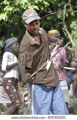 FOND BAPTISTE, HAITI - FEBRUARY 29, 2016:  Close-up of an unidentified man stripping a stalk of sugarcane with a long-bladed knife.  He's at the market in Fond Baptiste, Haiti. - stock photo