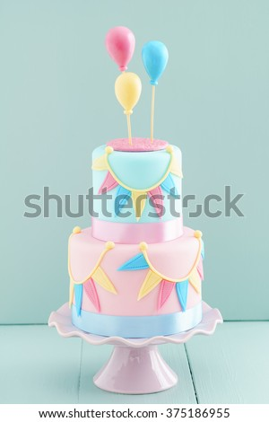 Fondant covered pastels coloured birthday cake with buntings and balloons - stock photo