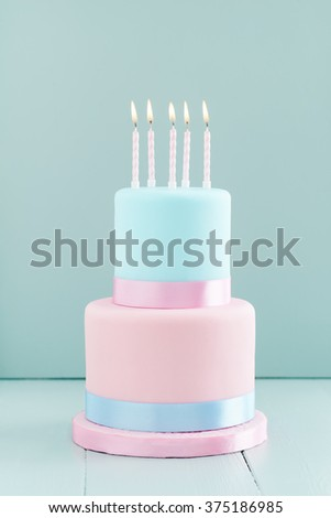 Fondant covered pastels coloured birthday cake with five birthday candles - stock photo