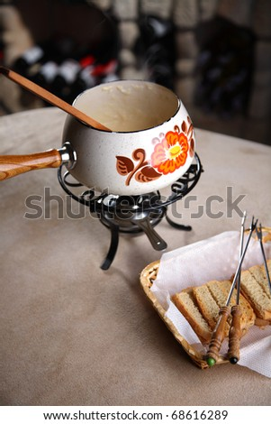 Fondue in a wine cellar. Crackers in a wattled basket with plugs - stock photo
