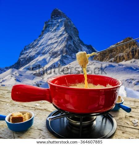 Fondue, traditional Swiss dish - Matterhorn in Swiss Alps in background - stock photo
