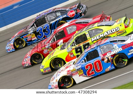 Fontana, CA - FEB 20, 2010:  Kevin Harvick, James Buescher, Paul Menard and Joey Logano make it four wide through the turns during the Stater Bros 300 race at the Auto Club Speedway on Feb 20, 2010 - stock photo