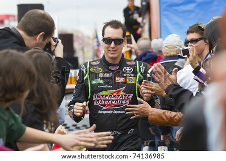 FONTANA, CA - MAR 27: Kyle Busch (18) walks through the line of fans before the start of the Auto Club 400 NASCAR Sprint Cup race at the Auto Club Speedway in Fontana, CA on Mar 27, 2011. - stock photo
