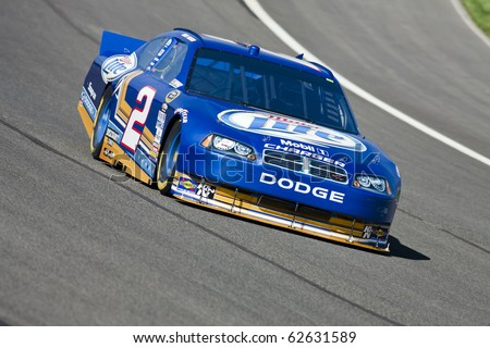 FONTANA, CA - OCT 08, 2010:  Kurt Busch brings his Miller Lite Dodge through turn 4 during a practice session for the Pepsi Max 400 race at the Auto Club Speedway in Fontana, CA on Oct 8, 2010. - stock photo