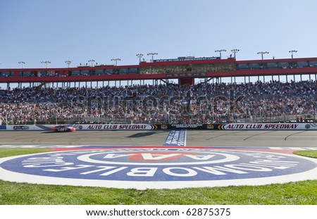 FONTANA, CA - OCT 10:  Tony Stewart holds off the rest of the Sprint Cup teams to win the Pepsi Max 400 race at the Auto Club Speedway in Fontana, CA on Oct 10, 2010. - stock photo