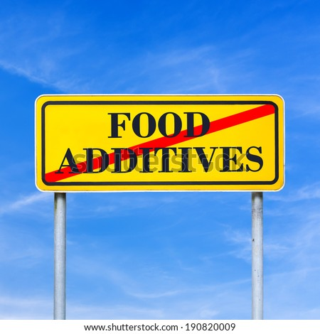 Food additives prohibited - conceptual image with the words Food additives crossed through in red on a yellow traffic sign against a sunny clear blue sky. - stock photo