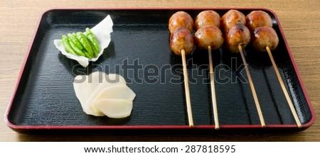 Food and Cuisine, A Plate of Thai Grilled Sausages on Wooden Skewer Served with Pickled Ginger, Cabbage and Chili Pepper. - stock photo