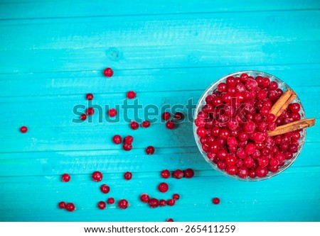 Food and drink, still life concept. Frozen red currant berries in a glass bowl with cinnamon on a wooden table. Selective focus, copy space background, top view, vignette - stock photo