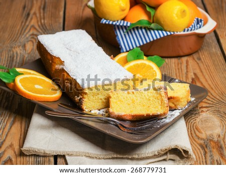 Food and drink, still life concept. Home made orange cake with citrus fruits on a wooden table. Selective focus - stock photo