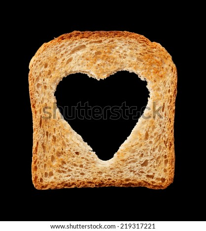 Food and health concept - bread slice with heart shaped hole - isolated on black - stock photo