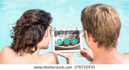 Food app against couple using digital tablet - stock photo