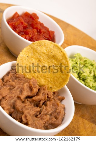 Food Appetizers Chips and Salsa Refried Beans Guacamole on Wood Cutting Board  - stock photo