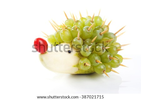 Food art creative concepts. Funny and cute hedgehog made of pear, green grapes and tomato nose isolated on a white background. - stock photo