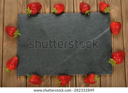 Food background, black slate and strawberries - stock photo