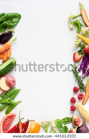 Food background border flat lay of rainbow coloured fresh fruits and vegetables, carrot chilli cucumber purple cabbage spinach rosemary herb, plenty of copy-space - stock photo
