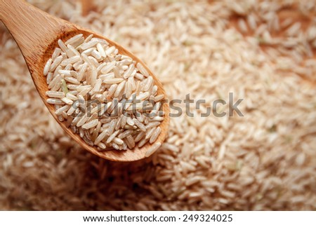 food background. brown rice in a wooden spoon. top view - stock photo