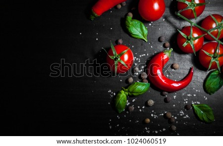 food background. red chili peppers, cherry tomato, basil, black pepper, salt on dark wooden background with copy space. top view