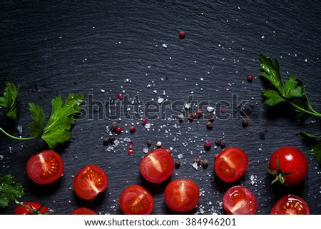 Food background, sliced and whole cherry tomatoes, parsley, sea salt, black and pink pepper, on a dark stone background, view svrehu - stock photo