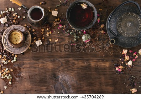 Food background tea and coffee theme. Different black and green dry tea, different coffee beans, cup of hot tea and coffee,  teapot over dark wooden background. Top view. Space for text - stock photo