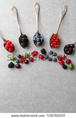 Food background with berries and spoons, healthy concept