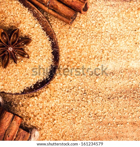 Food background with copy space. Brown sugar, anise star and cinnamon sticks on wooden background close up, still life.