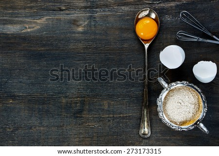 Food background with copy space - egg yolk in vintage spoon and flour in vintage cup on wooden texture. Top view. - stock photo