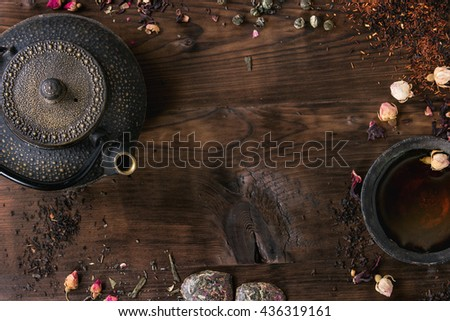 Food background with different black and green dry tea, rose buds cup of hot tea and iron teapot over dark wooden background. Tea drinking concept. Top view. Space for text.