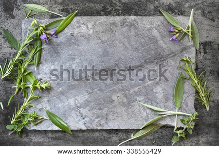 Food background with fresh herbs on dark slate.  Overhead view. - stock photo