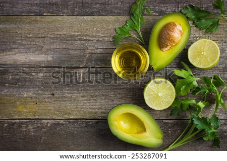 food background with fresh organic avocado, lime, parsley and olive oil on  old wooden table, top view, copy space - stock photo
