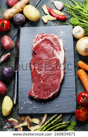 Food background  with fresh vegetables and raw beef steak. Slate and wood background.  - stock photo