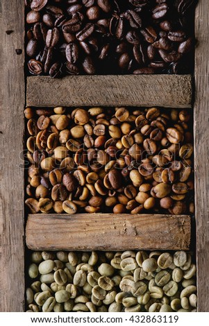 Food background with green and brown decaf unroasted and black roasted coffee beans in old wooden box. Top view. Close up