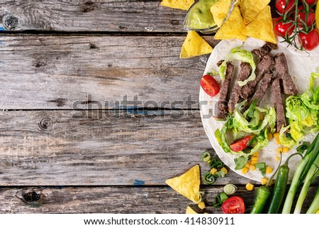 Food background with nachos chips and ingredients for making tortilla. Onion, tomatoes, chili peppers, beef, tortillas and corn with deeps over old wooden surface. Flat lay with copy space - stock photo