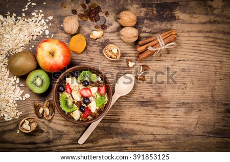 Food background with oatmeal in bowl and fruits on old wooden table, space for text - stock photo