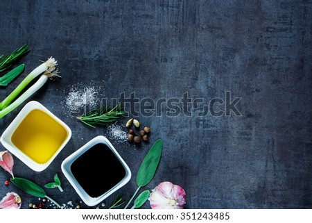 Food background with olive oil, vinegar, peppercorns, sea salt, garlic and rosemary on dark vintage texture. Top view. Herbs and spices selection. Cooking, Healthy Eating or Vegetarian concept. - stock photo