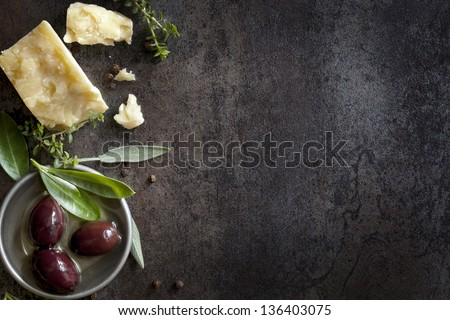 Food background with parmesan cheese, fresh herbs and olives, over dark slate.  Lots of copy space. - stock photo