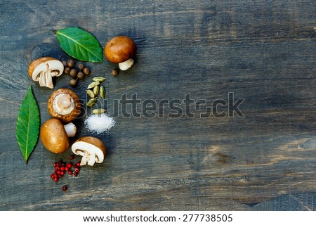 Food background with spices, herbs and fresh mushrooms on dark wooden table. Space for text. Top view. - stock photo