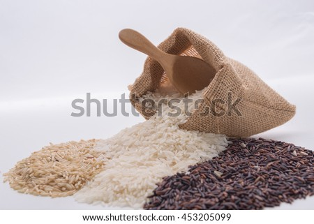 Food background with three rows of rice varieties : brown rice,riceberry rice, white (jasmine) rice. - stock photo