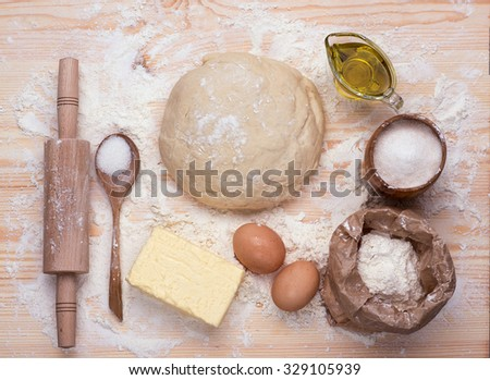 Food baking background. Ingredient of  homemade baking on wooden table. Wheat, eggs, sugar, salt, butter, oil, rolling-pin, spoon.