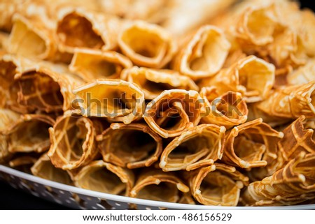 food, baking, cooking and eating concept - close up of waffle cones or rolls