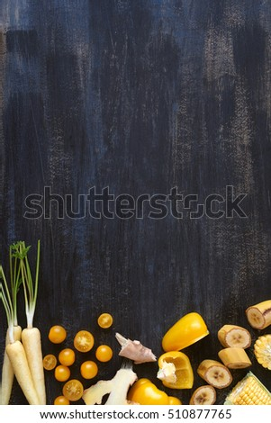 Food border constructed with yellow fruits and vegetables, fresh raw organic produce on dark distressed background