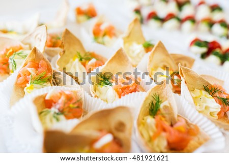food, catering and unhealthy eating concept - close up of dough cornet with salmon fish filling