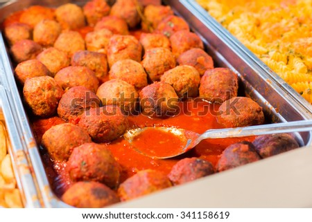food, catering, self-service and eating concept - close up of meatballs and other dishes on metallic tray - stock photo