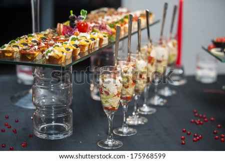 Food catering - set service with Caesar salad in glass cups and finger food at restaurant before party - stock photo
