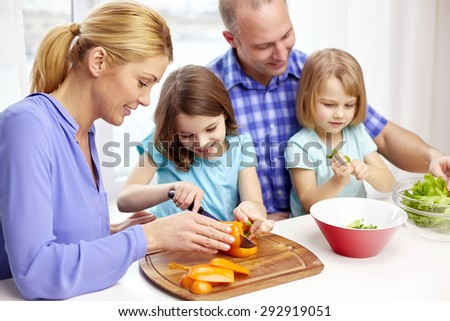 food, children, culinary and people concept - happy family with two kids cooking vegetables at home - stock photo