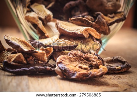 Food. Closeup dry mushrooms spilling out from storage jar on wooden surface table background. - stock photo