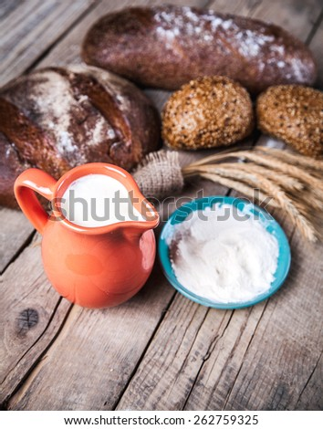 food. composition of bread, spike, flour and milk on wooden background - stock photo