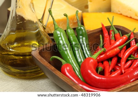 Food composition. Red and green peppers and olive oil jar.