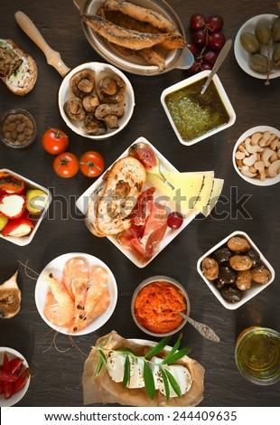 Food Concept - Wide Variety Appetizing Tapas on Top of Brown Wooden Table - stock photo